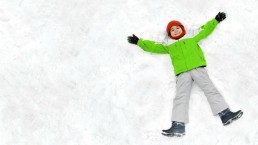 boy making snow angel happy holidays