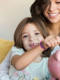 girl putting allowance in piggy bank Q Wuncer