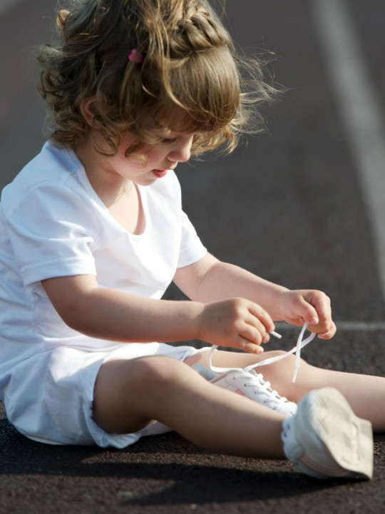 girl tying shoes independent kid